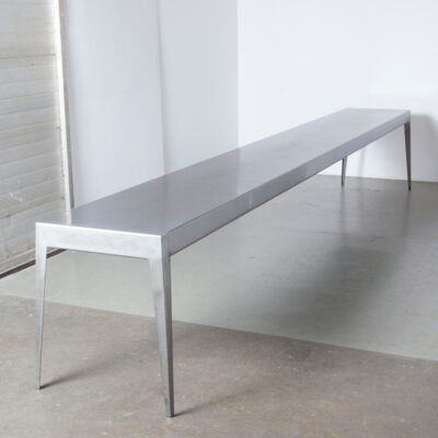 Nel Verschuuren Schouwburg Amstelveen Foyer Tafel Joosten Projecten folded heavy gauge sheet steel clear coat one piece gun metal silver sturdy minimalistic modern splayed legs custom made not commercially available heavy duty built to last solid stable made-to-order exclusive architect designed